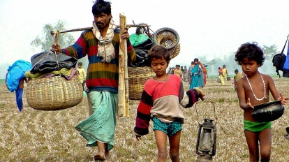 ** FILE ** A deportee along with his two children, caught in row over their nationality, walks with their belongings in Satgachi near the India-Bangladesh border in the Indian state of West Bengal, in this Feb. 4, 2003 file photo. Hundreds of thousands of people are stuck in tiny enclaves inside each others country. Largely forgotten by their own countries, there are 111 pockets of Indian territory inside Bangladesh, and 51 bits of Bangladesh inside India. (AP Photo/Anupam Nath, File)