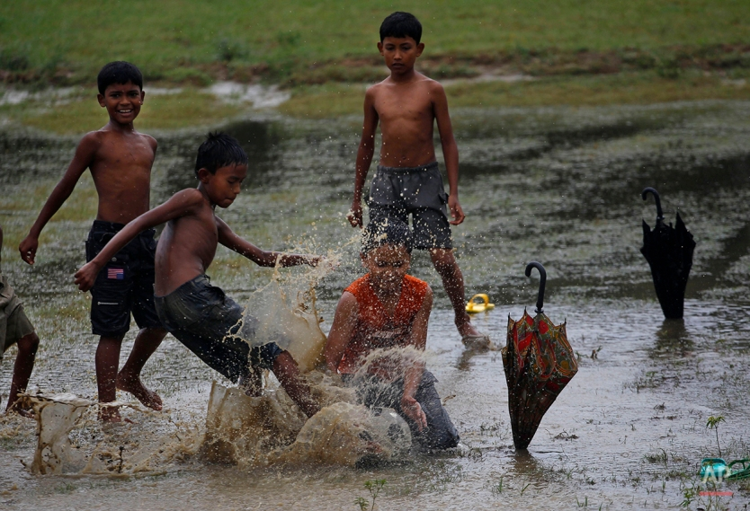 Using umbrellas as goal posts, children play soccer after heavy rains in Taknaf, Bangladesh, Thursday, June 21, 2012. (AP Photo/ Saurabh Das)