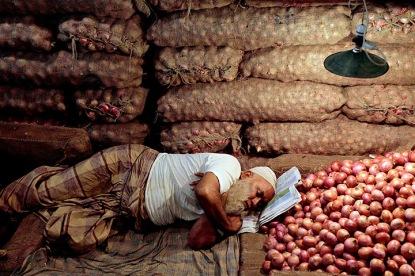 Dhaka, Bangladesh: A shopkeeper sleeps in his onions shop at Karwanbazer wh