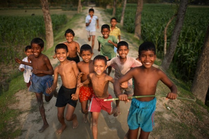 Children run and play in the Dawabari river bed area. 'Chars' such as this - islands that are periodically submerged by the country's mighty rivers - are home to over five million people in Bangladesh. Life for the char dwellers is hazardous and uncertain. Flooding is common, as is loss of land and erosion, making it a struggle to grow enough food, and meaning families often need to relocate.